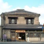 旧名取高三郎商店 明治39年の建築で、木骨石造り2階建てです。外壁に軟石を張り、両袖に卯建を建て、窓に土塗りの防火戸を付け、屋根が瓦葺きであります。角地にあるため、建物が2方に開けていて、2階の石壁に対して1階部分が開放的に構成できたのは、木軸組に石を貼り付けた木骨石造という構造ならでの技術であります。