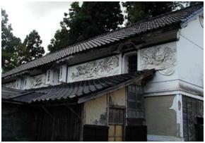名越家土蔵の「波に二疋龍」 明治40 年代に製作したと推定されている。縦1.8 m(1 間)・横18 m(10 間)・厚みは18 ㎝(6 寸) になる。龍の鱗は1 枚1 枚、塗込まれ陰影がある。完成まで2 ~ 3 年を要したいという。2 階窓にある 観音扉の鏡には、「三階松」「磯千鳥」がその上部に、唐破風の庇屋根が付いている。互いに向き合う 龍は波しぶきあび躍動的である。鏝絵は壁面から15 ㎝も飛び出して塗られている。竹内源造の鏝絵は、 長八と異なり肉厚で、建物に付随して鑑賞できるように構成されている。